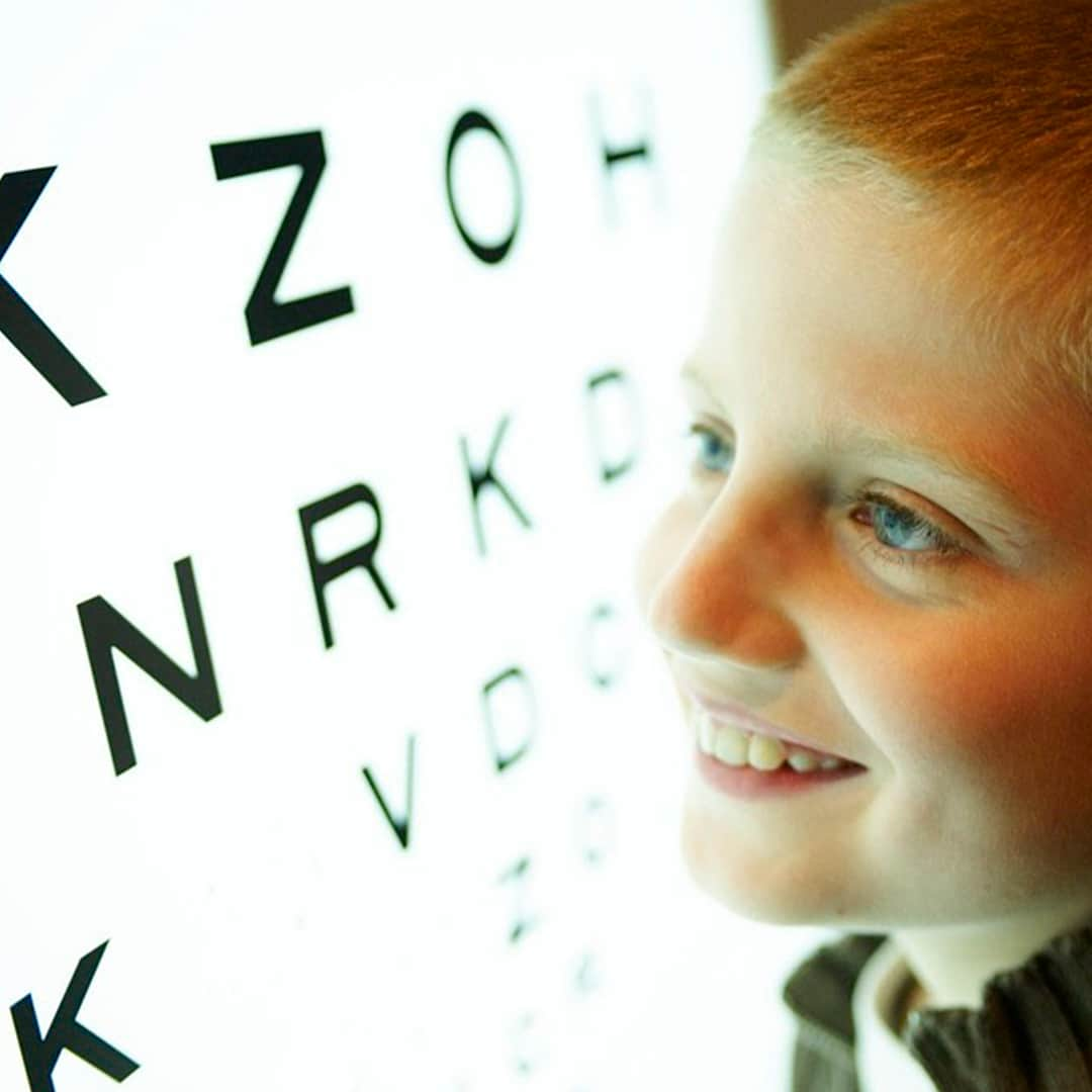 Boy smiling in front of eye chart